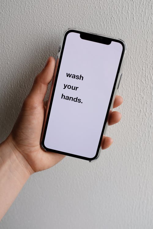 Crop faceless person showing smartphone screen with inscription near wall