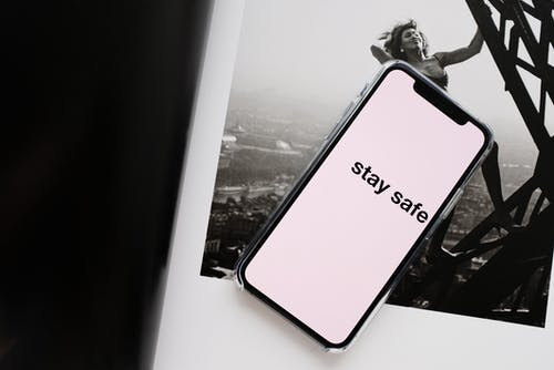From above of cellphone pale pink screen with STAY SAFE inscription put on open magazine with photo of cheerful woman climbing metal tower in city