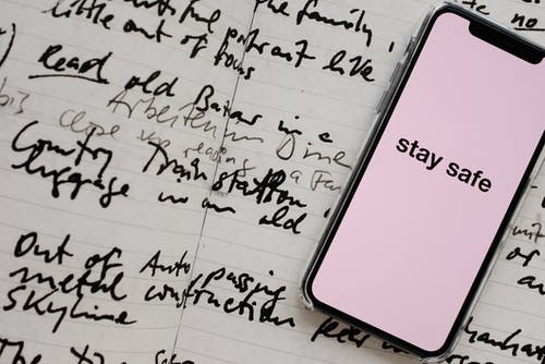 Smartphone screen with STAY SAFE inscription put near open copybook