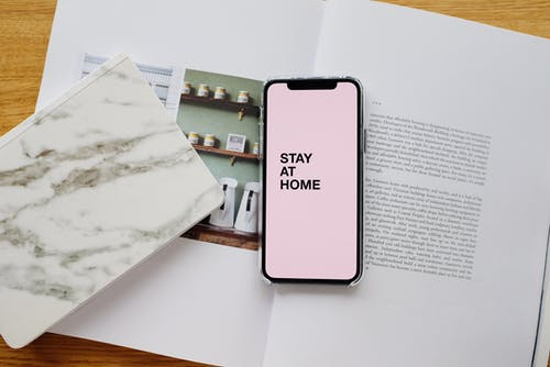 Top view of modern cellphone with pale pink screen and STAY AT HOME inscription placed on open magazine near notebook on wooden table during COVID 19 pandemic
