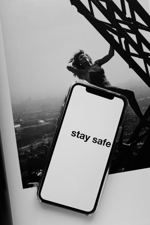 From above of cellphone with STAY SAFE inscription placed on open book with black and white photo of female model climbing tower in city