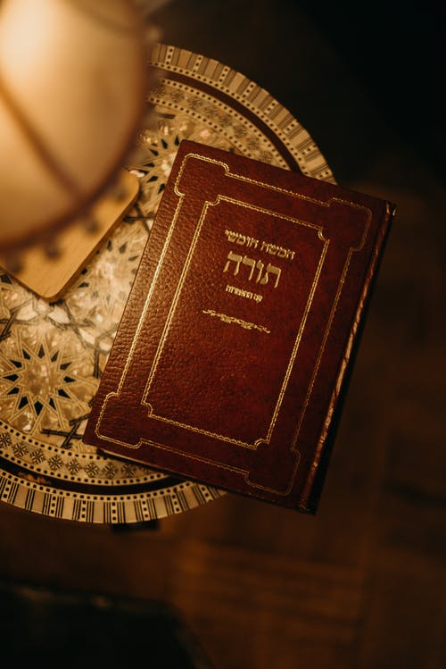 Book in Hebrew Next to a Lamp