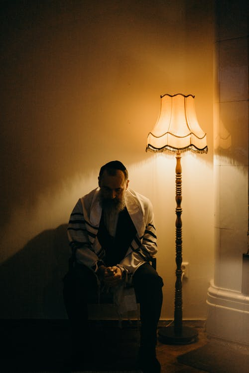 Bearded Man Sitting Next to a Lamp