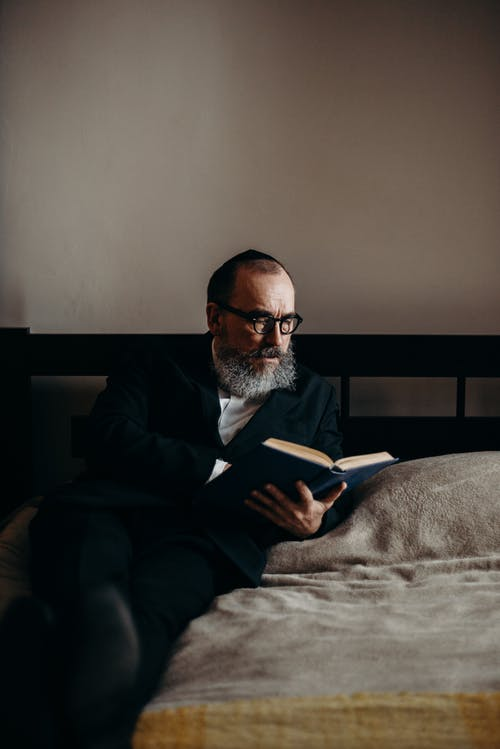 Bearded Man Reading a Book in Bed