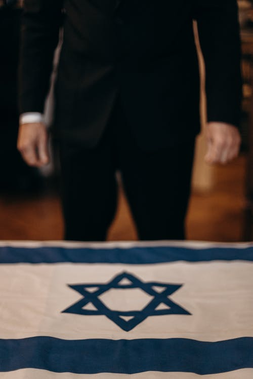 Man Standing next to the Flag of Israel