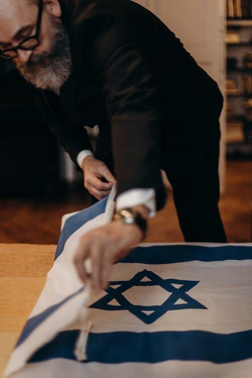 Bearded Man Folding the Flag of Israel