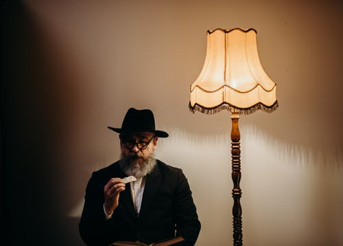 Man With a Hat Next to a Lamp