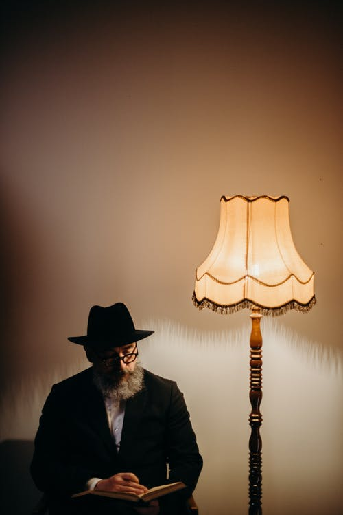 Photo Of An Old Man Beside Lamp