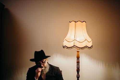 Photo Of Man Eating Beside Lamp