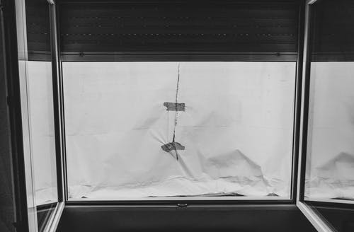 Grayscale Photo Of An Open Window Covered With Paper