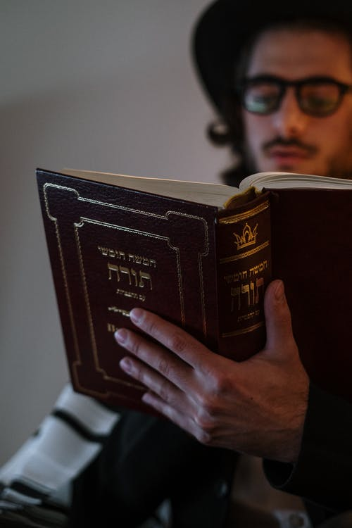 Young Man Reading a Book in Hebrew