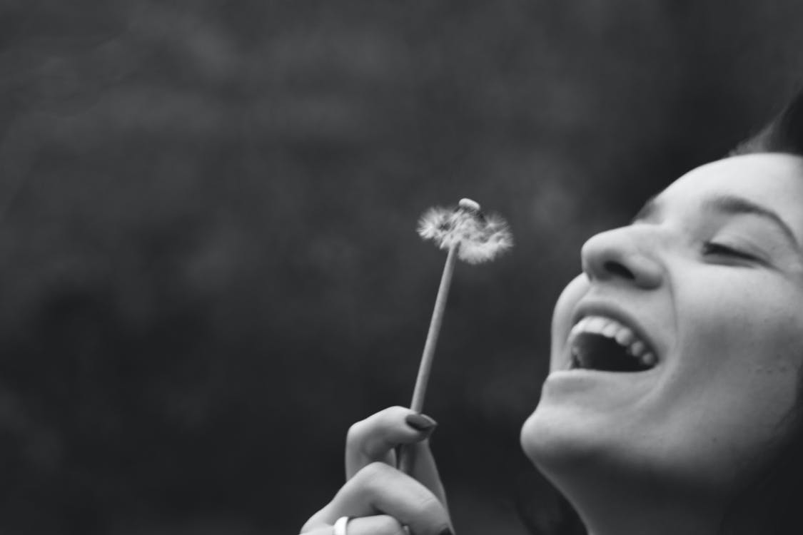 Smiling Woman Holding Dandelion Flower