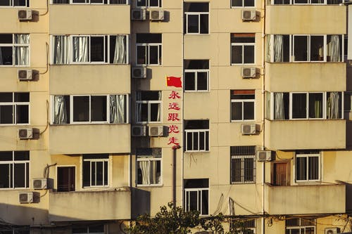 Facade of high building with red Chinese inscription in residential area in light of sun