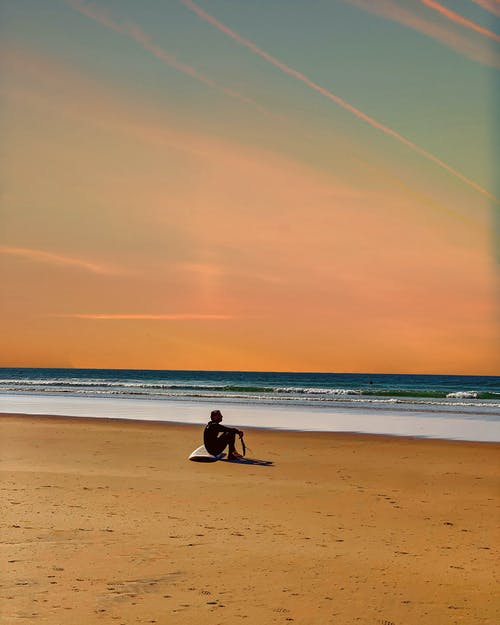 Man Sitting on Beach Shore During Sunset