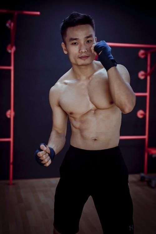 Muscular Asian boxer preparing to hit