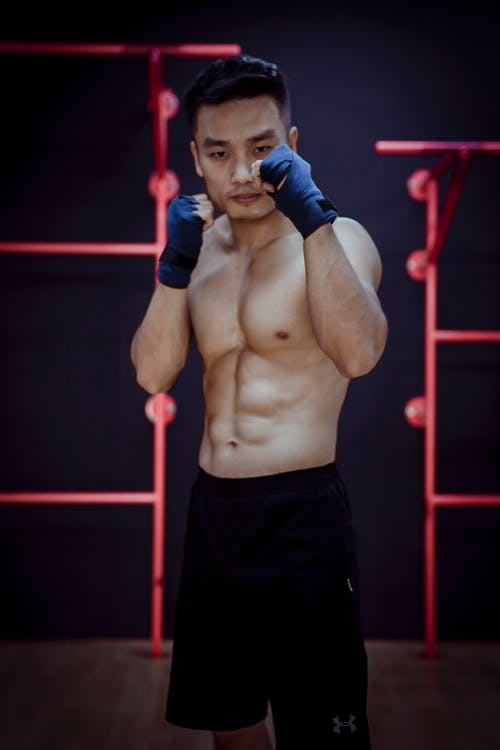 Pensive Asian fighting man training in gym