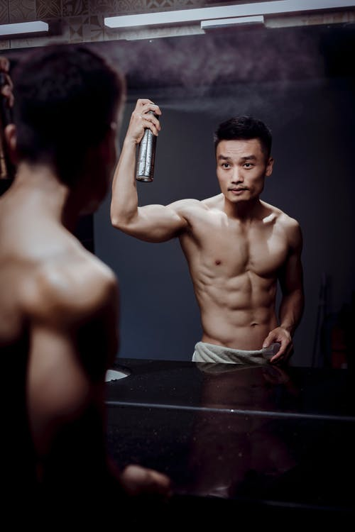Topless Man Holding Spray Bottle