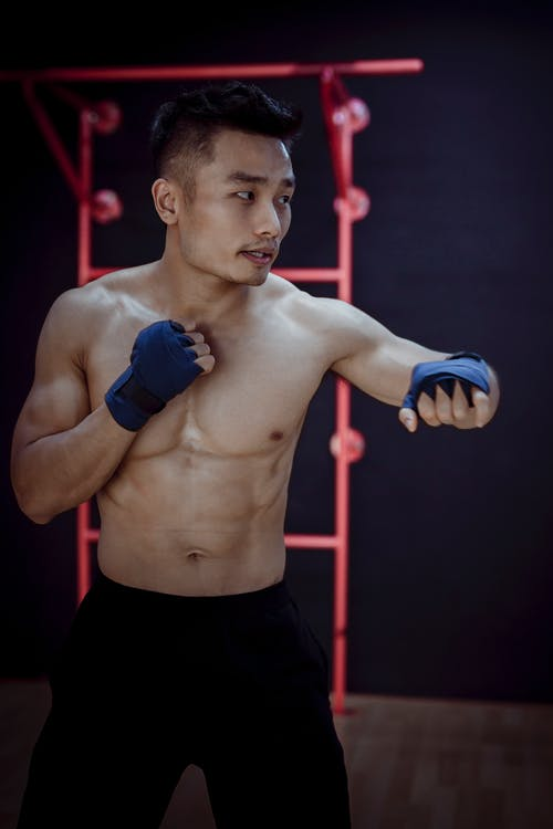 Muscular young naked Asian bodybuilder thoughtfully looking away while practice Muay Thai while training in gym