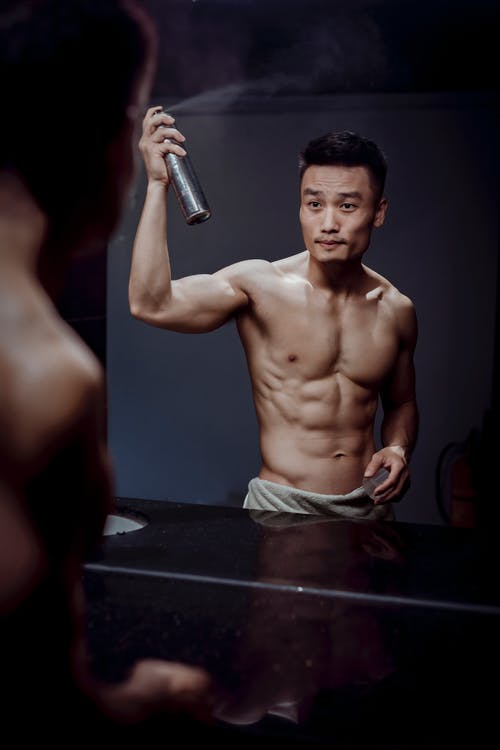 Muscular male athlete reflecting from mirror