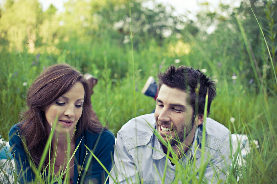 Man and Woman Lying on Grass Field