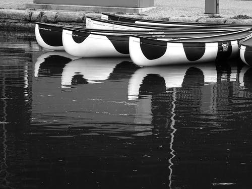 Three White-and-black Boats on Body of Water