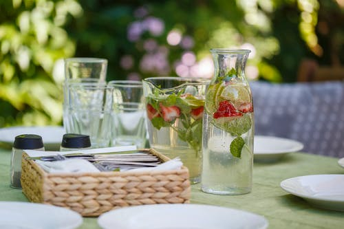 Set of water with lemon and strawberry composing with white plates and tools for eating food