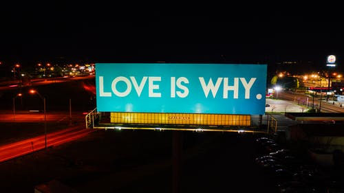 Blue billboard saying Love is why placed on road surrounded by cars and street lights against black night