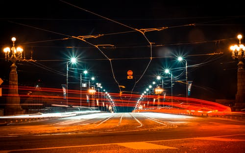 Picturesque long exposure of broad road with red light of fast traffic under street lamps on bridge at night