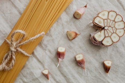 Close-Up Photo Of Sliced Garlic Beside Pasta