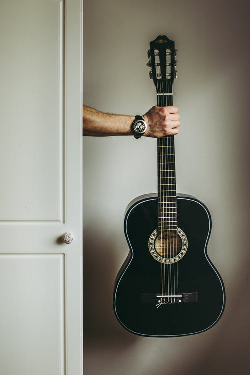 Person Holding Black Acoustic Guitar