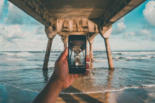 Ilmainen kuvapankkikuva tunnisteilla aallot, hiekkaranta, kamera, käsi
