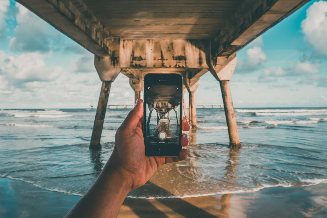 Person on Seashore Under Beach Dock While Holding Iphone