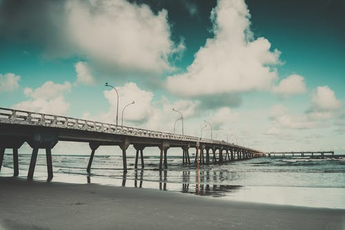 White Clouds and Gray Concrete Bridge Near at Seashore