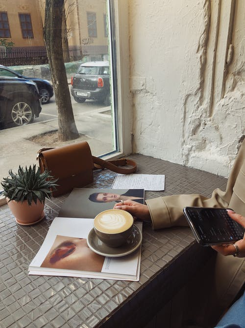 Crop of unrecognizable female tourist in casual wear surfing internet and flipping magazine while drinking coffee in sidewalk cafe