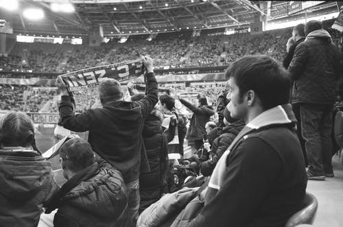Black and white of group of people in warm clothing standing at stadium and watching match