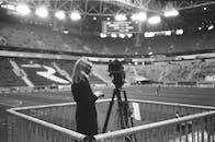 Female camera operator working at stadium