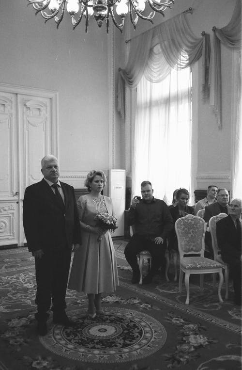 Elegant bride with groom in suit standing during wedding ceremony