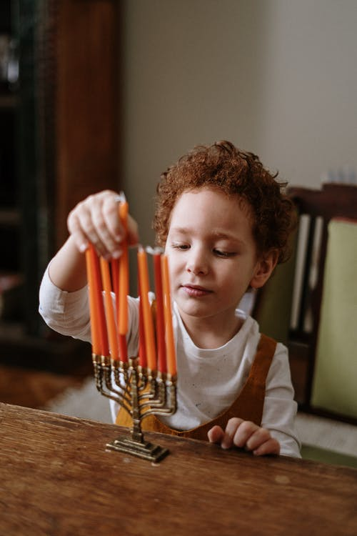 Boy Putting Candles in a Menorah