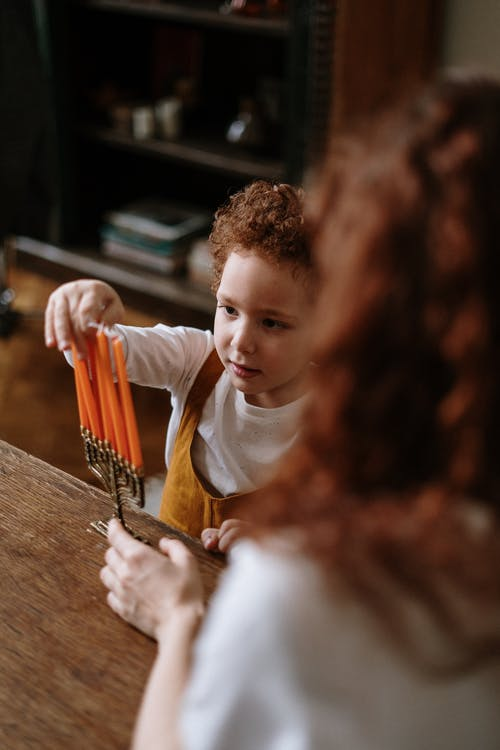 Child Touching a Menorah