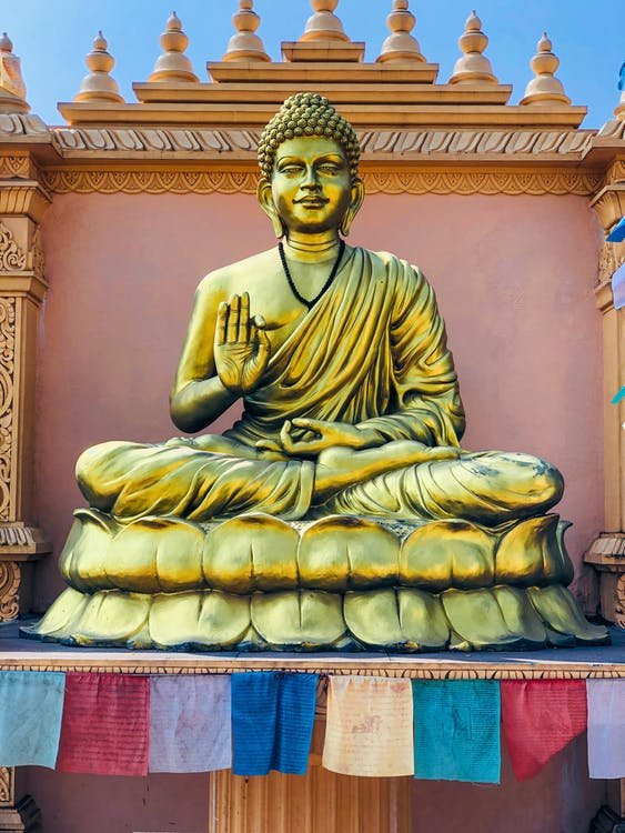 Golden Buddha Statue on Red and Blue Textile