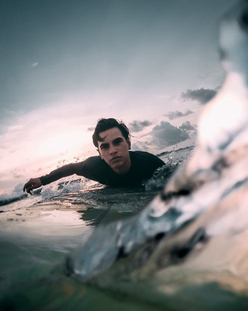 Man in Black Tank Top Swimming on Water