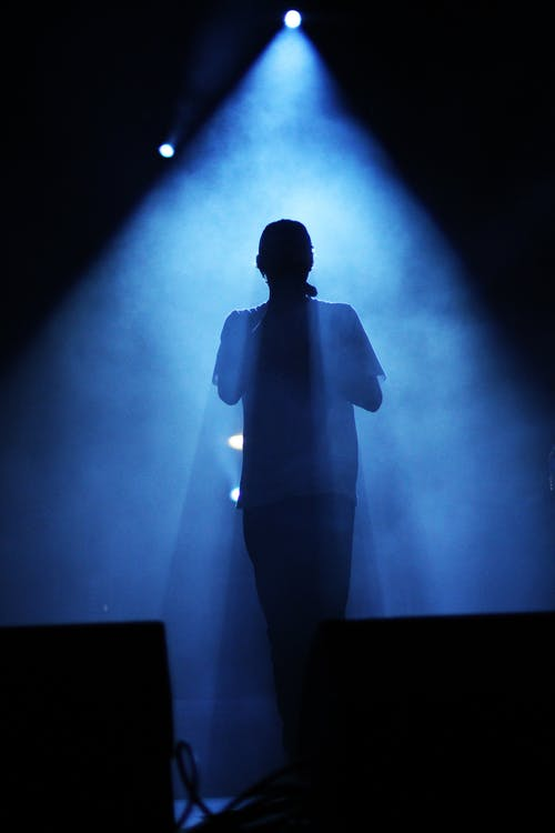 Silhouette of Man Standing on Stage