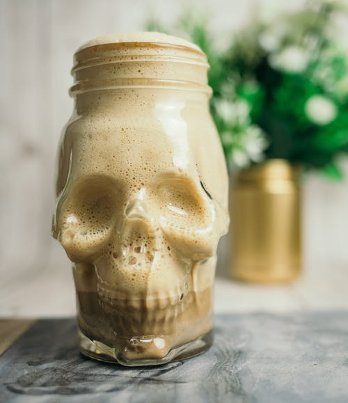Skull jar with coffee with milk on table