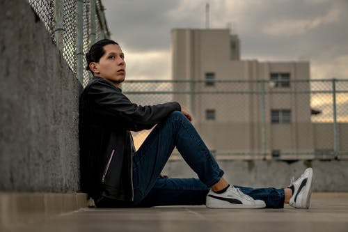 Man in Black Jacket and Blue Denim Jeans Sitting on Concrete Floor