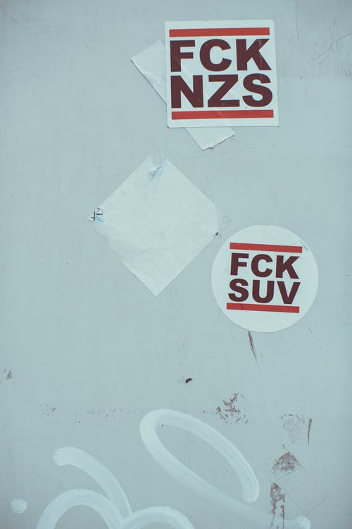 Shabby wall with rebel stickers against authorities