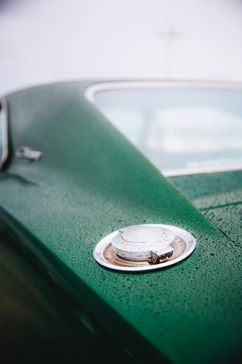 Selective focus of fuel cap of classy green car covered with raindrops in foggy weather
