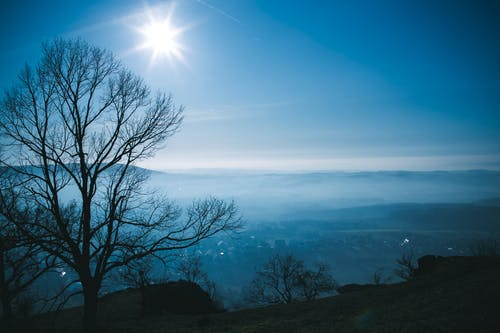 From above of valley covered with fog among hills under blue sky with bright sun