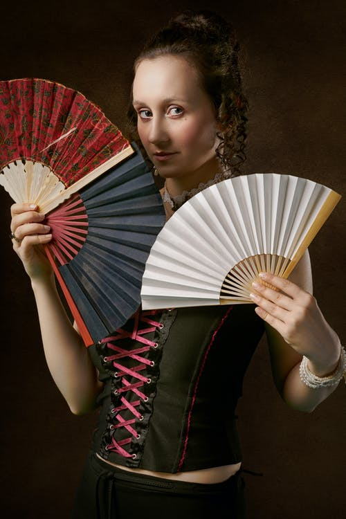 Woman Holding Two Hand Fans