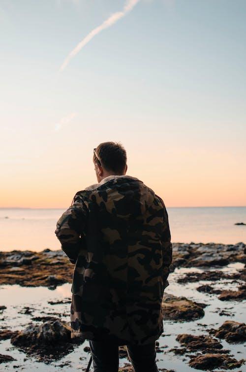 Male traveler standing on stony shore
