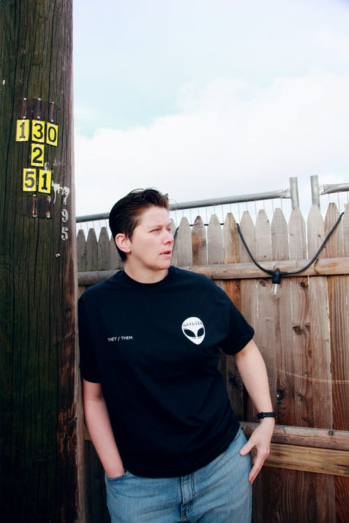 Man in Black Crew Neck T-shirt Standing Beside Brown Wooden Fence